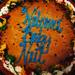 "A photo of a cookie cake that Everett's Aunt Jen and Uncle Casey brought to the hospital after he was born. It has colorful icing and blue letters that read ""Welcome Baby Neil"""