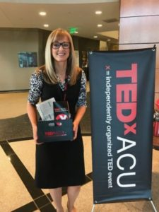 A picture of me standing next to a TEDxACU banner holding all of my swag!