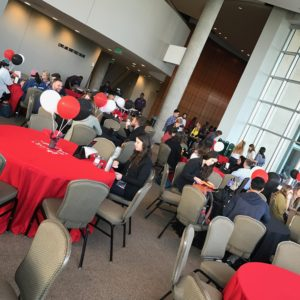 A photo of the gathering room at TEDxACU (Fulks Theater). Red, black and white balloons cover the tables, as well as red table cloths (signature TED colors). People are gathering at the table and breakfast buffet before the big show.