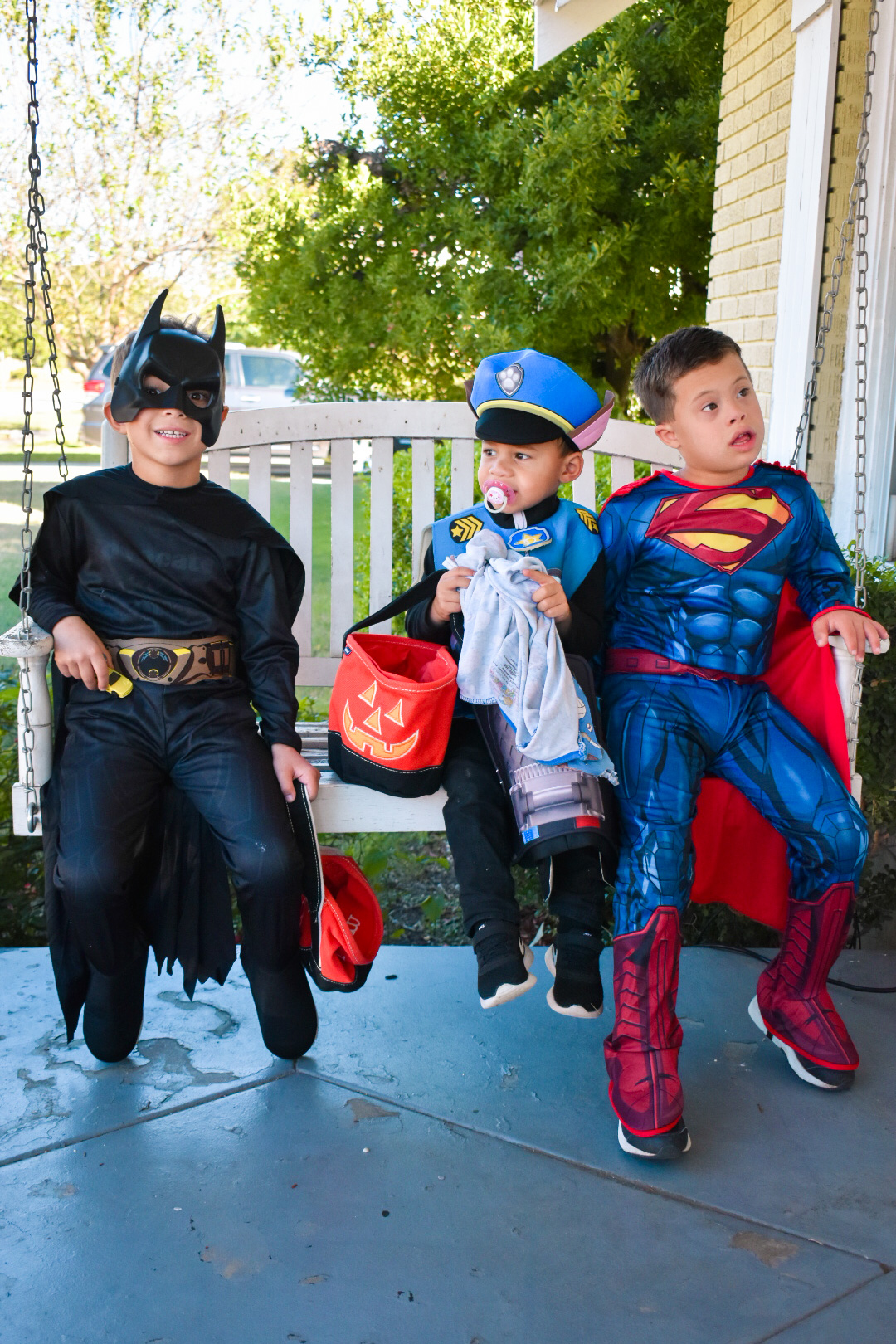 Three little boys dressed up as Chase from Paw Patrol, Superman, and Batman for halloween