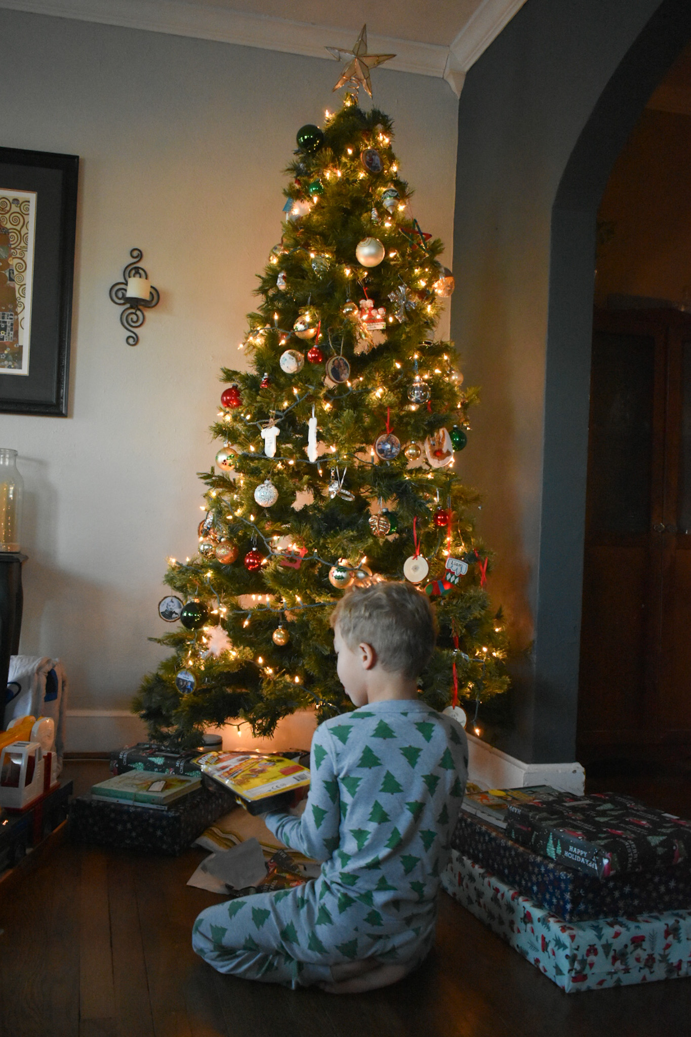 One little boy opening up presents by the family tree
