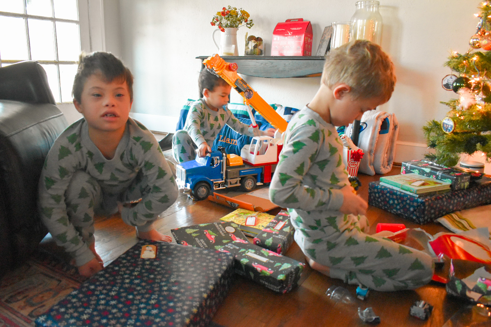 Three little boys opening up presents by the tree